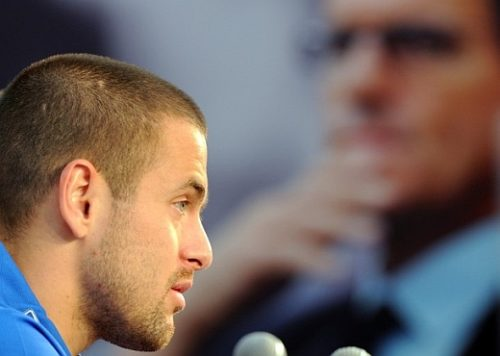 Joe Cole with an image of Capello looking over him